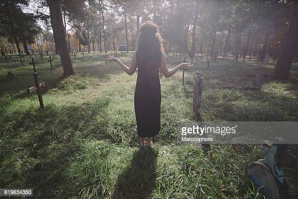 Lady in black dress standing on sunlight at graveyard.