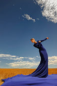 Lady in blue dress against sky portrait