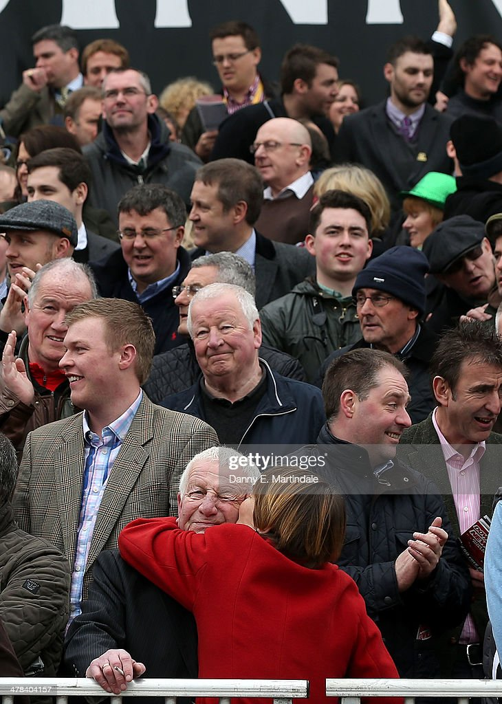 A lady in red hugs her husband after winning the second race of the day on day 3 of The Cheltenham Festival at Cheltenham Racecourse on March 13, 2014 in Cheltenham, England.