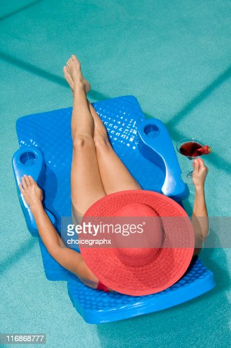 Lady in Red Swim Suite Floating at Swimming Pool