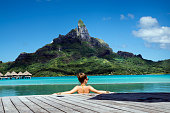 lady in the infinity pool  on the beach of a luxury vacation resort in the lagoon and looking on the Otemanu mountain on the tropical island of Bora Bora, near Tahiti, French Polynesia, Pacific ocean
