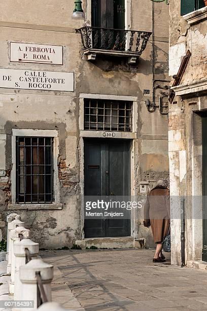 Lady in wintercoat entering Venetian alley
