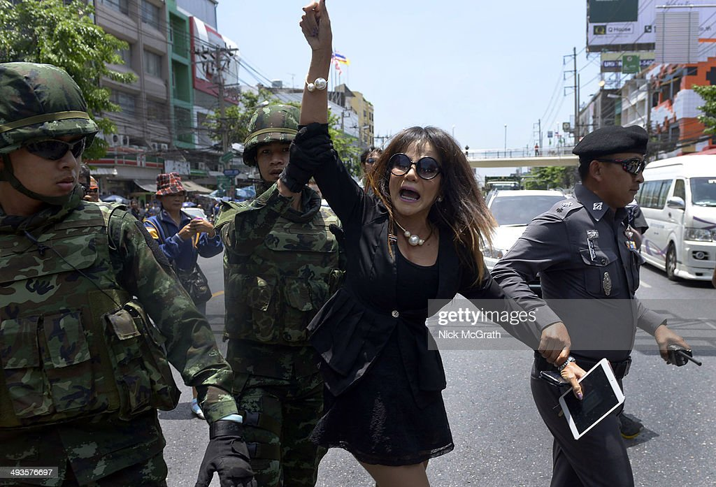 A lady is escorted by military officers and a policeman after a confrontation with anti coup protestors on May 24, 2014 in Bangkok, Thailand. Protestors marched into central Bangkok today to vent their anger two days after the military announced a coup d'etat and placed a curfew over the nation. The military has disbanded the country's senate and placed all law making authority in the hands of the army general.
