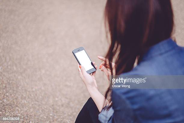 A lady is using smart phone in a park