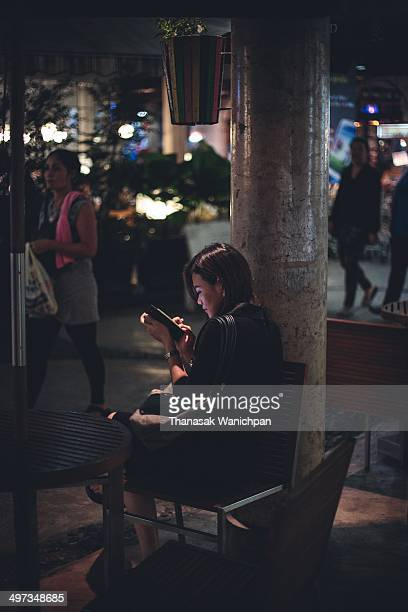 A lady is waiting for someone to dinner with and playing the internet on her smart phone at a shopping mall
