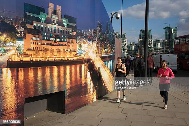 Lady joggers run past CCTV a camera and a construction hoarding a night time panorama of the Thames south bank featuring the HQ of the intelligence...