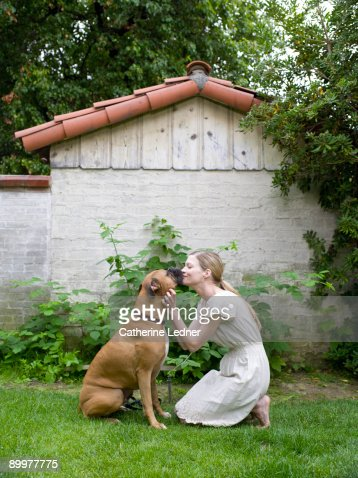 Lady Kissing her Boxer (Canis lupus familiaris) : Stockfoto