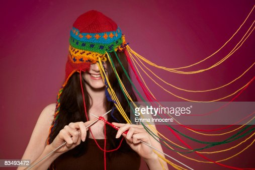 Lady knitting on her own hat