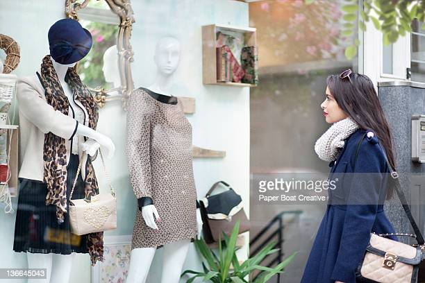 Lady looking at mannequin in window shop