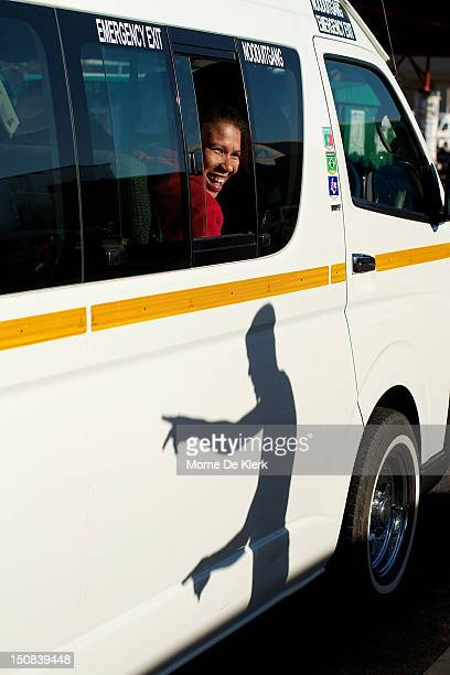 A lady looks on as the driver of a taxi calls for more commuters to get into his taxi on July 19 2012 in Upington South Africa Minibus taxis wait at...