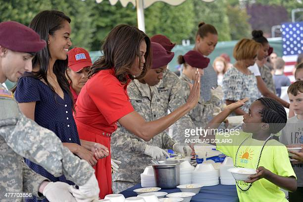 US Lady Michelle Obama flanked by her daughter Malia gives a high five to a young girl during a lunch with soldiers and guests as part of her visit...