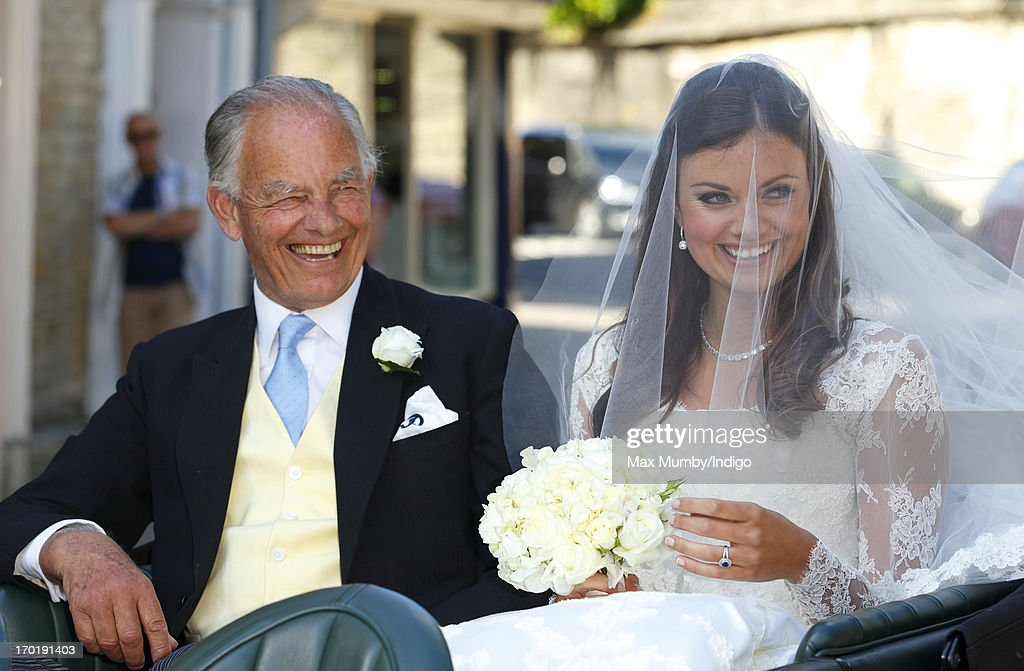 Lady Natasha Rufus Isaacs, accompanied by her father Marquess of Reading Simon Rufus Isaacs arrive at the church of St John the Baptist for her and Rupert Finch's wedding on June 8, 2013 in Cirencester, England.