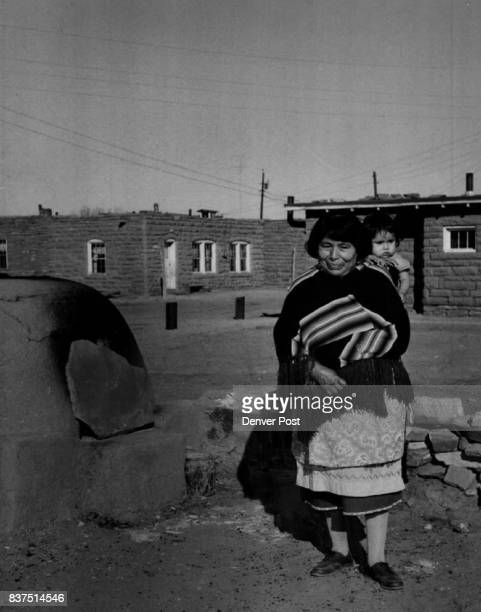 A lady of the Pueblo Mrs Lulu Hattie of Zuni pauses after inspecting her outdoor oven in preparation for Shalako baking She holds her small...