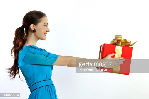 Lady offering a big red gift with a gold ribbon