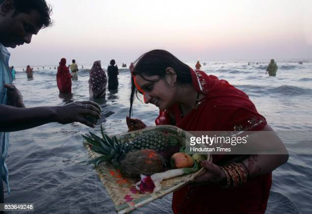 A lady offering prayers to the sun god on the occasion of Chhat Puja at Juhu beach on tuesday