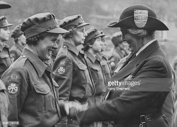 Lady Olave BadenPowell the Chief Guide of the World shaking hands with a Girl Guide following an inspection prior to overseas duty London February...