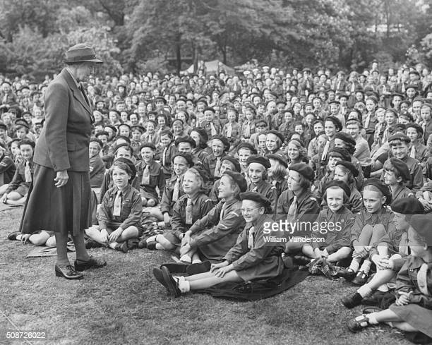 Lady Olave BadenPowell the Chief Guide of the World speaking to a group of Brownies sitting on the grass in the grounds of Lambeth Palace London May...