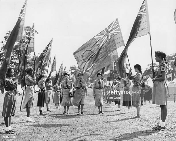 Lady Olave BadenPowell the Chief Guide of the World with Chief Commissioner Anstice Gibbs and Camp Commandant Elizabeth Severidge walking between two...