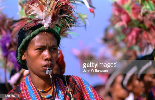 A lady performing a traditional Timorese dance, adorned with a feathered headdress and a brightly coloured costume.