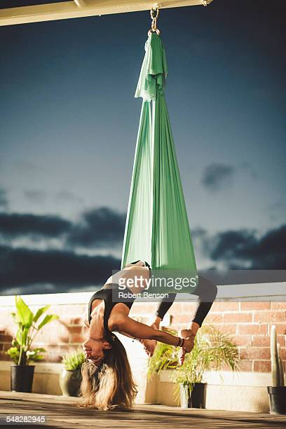 A lady performs aerial yoga.