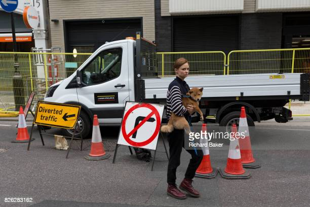 A lady pet owner safely carries her dog past construction bollards on 1st August 2017 in London England