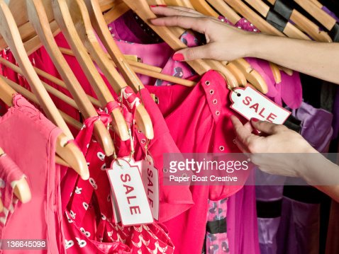 lady picking out dresses with a Sale tag on it