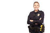 Female police officer posing with arms crossed against white background