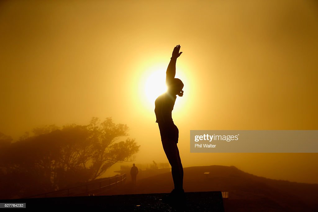 A lady practices yoga on the summit of Mt Eden as the sun struggles to shine through a blanket of fog over Auckland City on May 4, 2016 in Auckland, New Zealand. The morning fog disrupted flights and ferry services in the city.