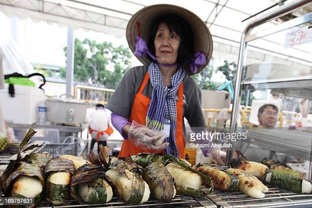 A lady prepares the Chuoi Nuong from Vietnam during the World Street Food Jamboree at the F1 Pit Building Paddock on June 1 2013 in Singapore This 10...