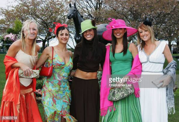 Lady race goers pose on Ladies Day during the Grand National Meeting at Aintree Race Course on April 8 2005 in Aintree England
