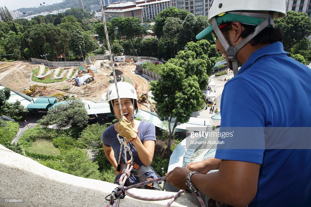 A lady reacts as she abseils at the Merlion at Sentosa during the OBS-The Merlion Charity Abseil on July 20, 2013 in Singapore. Abseiling The Merlion at Sentosa, an iconic national structure that stands at a formidable height of 37m, calls on donors to draw not just monetary contributions but also courage in literally stepping out of their comfort zone. All proceeds go to Life Community Services Society, a registered charity that takes care of disadvantaged children and at-risk youth from low income families and whose parents are incarcerated.