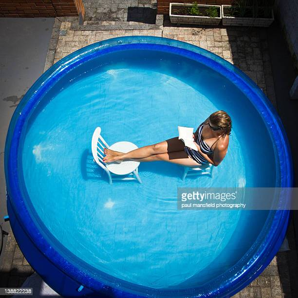 Lady reading book in paddling pool