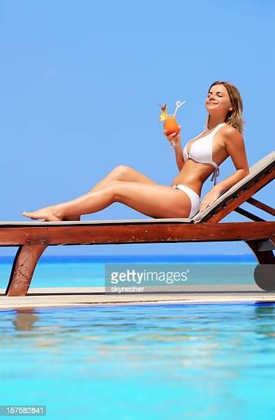 Femme se détendre dans le fauteuil dans un complexe exotique.