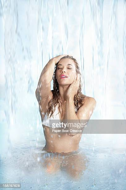 Lady relaxing under a soft waterfall
