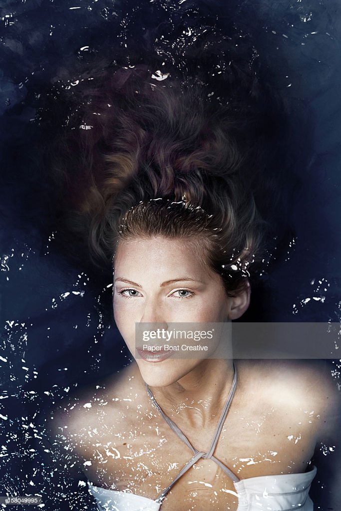 Lady resting in a swimming pool : Stock Photo