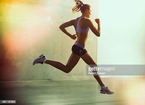 A lady runs in big stride.