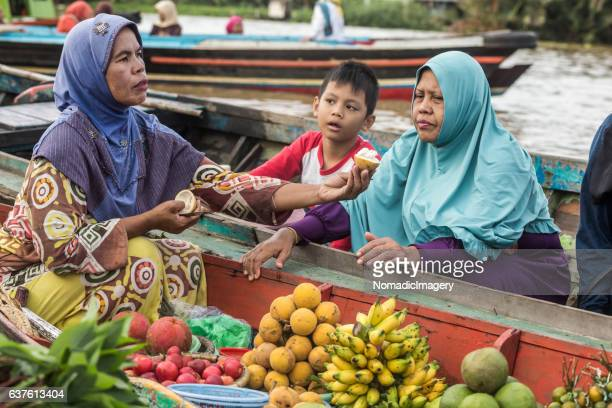 Lady selling fruit from a boat at a floating market