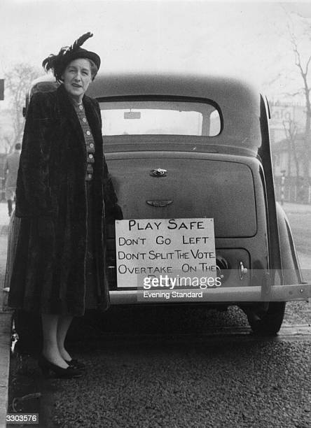 A lady standing by the rear of car with a sign stating 'Play safe Don't go left Don't split the vote Overtake on the right' during the 1950 General...