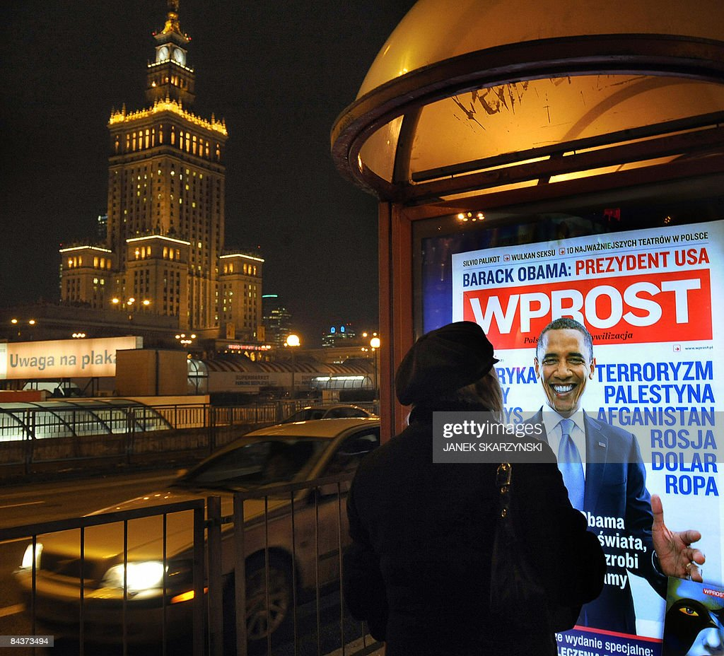 A lady stands in front of an advertisement for a Polish weekly magazine which cover carries a portrait of new US President <a gi-track='captionPersonalityLinkClicked' href=/galleries/search?phrase=Barack+Obama&family=editorial&specificpeople=203260 ng-click='$event.stopPropagation()'>Barack Obama</a> in a Warsaw street on January 20, 2009, on the day of Obama's inauguration. <a gi-track='captionPersonalityLinkClicked' href=/galleries/search?phrase=Barack+Obama&family=editorial&specificpeople=203260 ng-click='$event.stopPropagation()'>Barack Obama</a> took the oath of office to become the first black president in US history Tuesday, proclaiming America had chosen 'hope over fear' and must unite in a 'new era of responsibility' to triumph over its multiple crises.