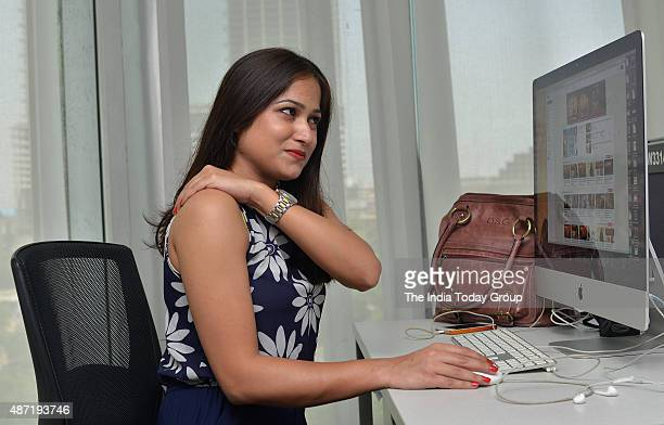 A lady suffering from back pain due to long sitting hours at office