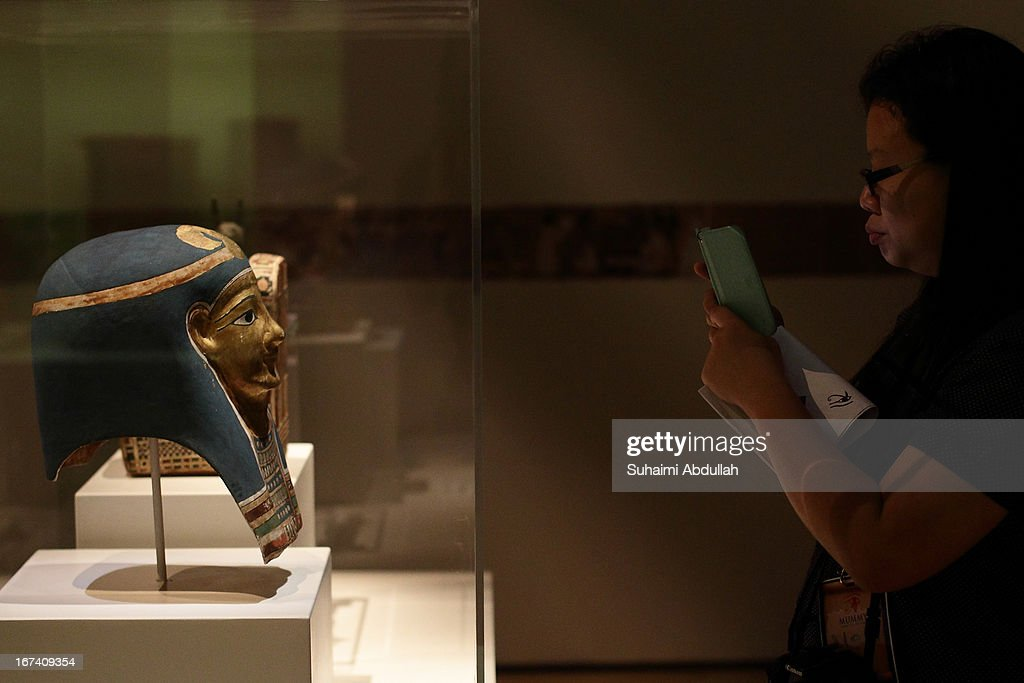 A lady takes a photo of the mummy face mask exhibit during a media preview of the Mummy: Secrets of the Tomb exhibition at ArtScience Museum on April 25, 2013 in Singapore. The exhibition includes more than 100 artifacts and six mummies from the heralded ancient Egyptian collection of the British Museum. Among the mummies displayed is the Egyptian temple priest, Nesperennub who lived 3,000 years ago. The exhibition will run from April 27 till November 4, 2013.