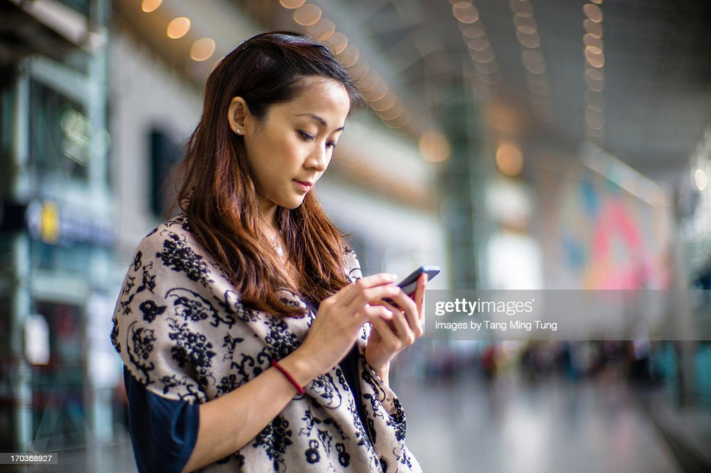 Lady using smartphone in train station