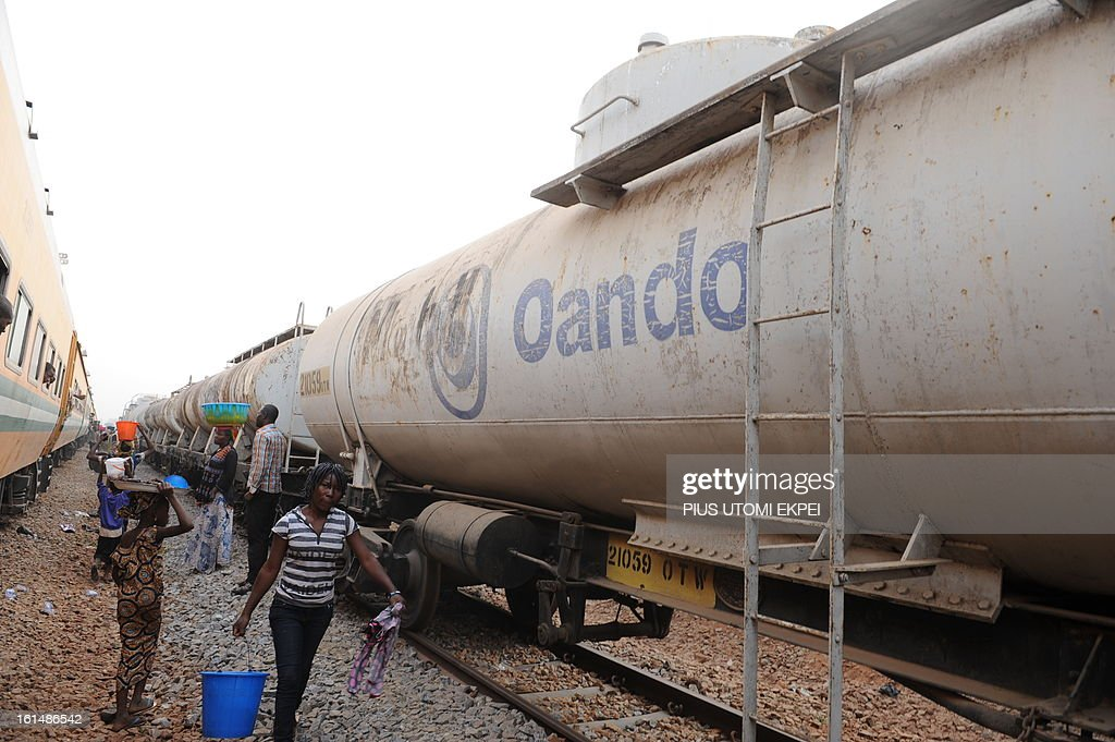 A lady walk past petroleum tanker wagon of the Nigerian Railway Corporation at Mokwa Station on February 8, 2013. The rejuvenated Nigerian Railway Corporation has resumed passenger and haulage services on the Lagos-Kano route following the refurbishing of engines and coaches over 20 years the corporation had gone bankrupt. Earlier last year, the corporation had acquired 20 pressurised tank wagons in preparation for the haulage of petroleum products from Lagos to northern parts of the country. The 20 wagons have the capacity to lift 900,000 litres of petroleum products, the equivalent of 27 road tankers.