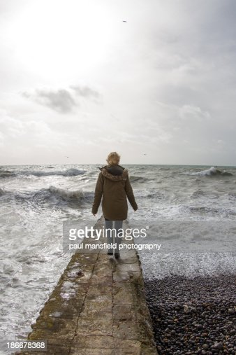 Lady walking on sea wall with rough sea