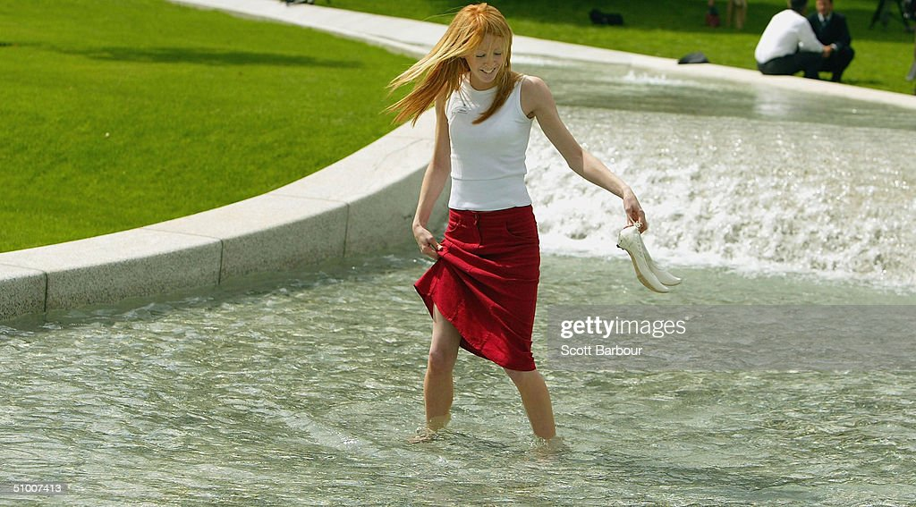 A lady walks in The Diana, Princess of Wales Memorial Fountain in Hyde Park on June 29, 2004 in London, England. The fountain by the American designer Kathrun Gustafson has been filled with water a week ahead of its ceremonial opening by the Queen.