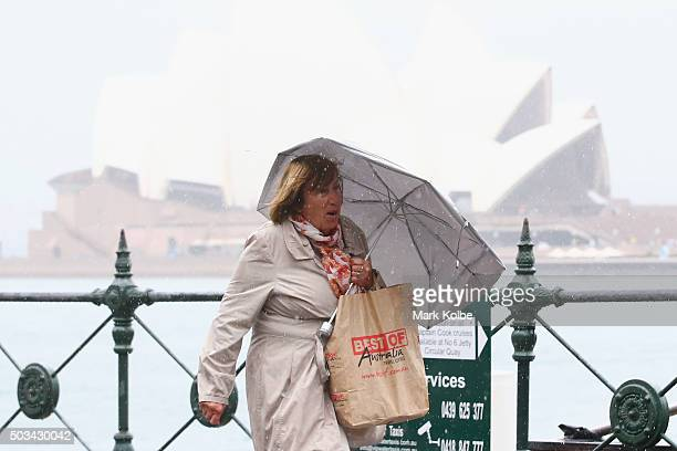 A lady walks with an umbrella to shelter from the rain through Circular Quay on January 5 2016 in Sydney Australia Sydney has experienced one of the...