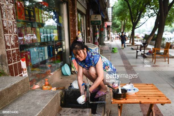 A lady washes dishes on the street in Huangshi center On Monday September 19 2016 in Huangshi Yangxin County China