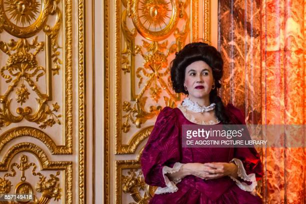 Lady wearing a wig and red dress courtship party with participants wearing clothes from the Louis XIV period Palace of Versailles France Historical...
