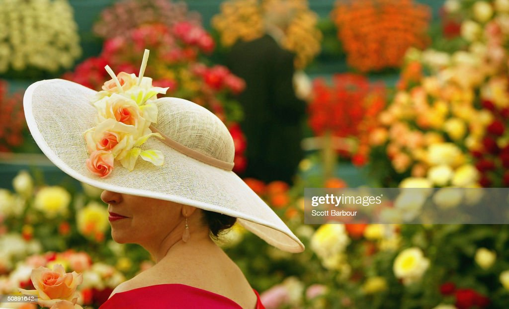 A lady wearing flowers in her hat looks at a display at the annual Chelsea Flower Show on May 24, 2004 in London, England. The show is due to open to the public on May 26 dates back to 1862.