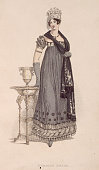 A lady wears a charcoalcolored evening dress with short puff sleeves and a decorated hem Her accessories include a black stole and a floral hat